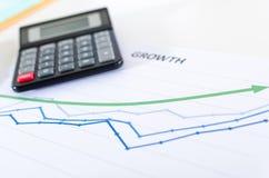 Οικονομικές γραφικές παραστάσεις που παρουσιάζουν αύξηση με τον υπολογιστή Στοκ φωτογραφία με δικαίωμα ελεύθερης χρήσης