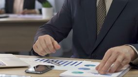 Οικονομικός διευθυντής που αναλύει δύο διαγράμματα και που κάνει τις σημειώσεις, επιχειρηματίας στην εργασία απόθεμα βίντεο