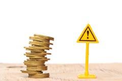 οικονομικός κίνδυνος Νομίσματα που πέφτουν και ετικέτα προειδοποίησης στο whitebackgrou Στοκ Φωτογραφίες