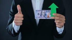 Οικονομικός σύμβουλος με τα τραπεζογραμμάτια δολαρίων που παρουσιάζουν αντίχειρες πάνω-κάτω, αύξηση απόθεμα βίντεο