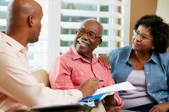 Οικονομικός σύμβουλος που μιλά στο ανώτερο ζεύγος στο σπίτι στοκ φωτογραφία