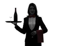 Οικονόμος σερβιτόρων γυναικών που η σκιαγραφία κόκκινου κρασιού στοκ εικόνες