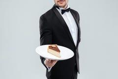 Οικονόμος στο πιάτο εκμετάλλευσης σμόκιν με το κομμάτι του κέικ στοκ εικόνες