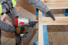 Οικοδόμηση ενός τοίχου για το σπίτι πλαισίων Πλαισιώνοντας Nailer χρήσης εργαζομένων για να συνδέσει τις ξύλινες ακτίνες Στοκ Εικόνες