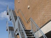 οικοδόμηση τούβλου κάτω από διαφυγών σύγχρονα σκαλοπάτια μετάλλων πυρκαγιάς τα κύρια Στοκ Φωτογραφία