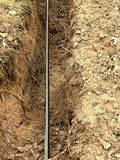 Οικοδόμηση των γραμμών μεταλλικών και καλωδίων οπτικών ινών Τοποθέτηση του υπόγειου καλωδίου σύνδεσης δικτύων ρυμούλκησης Στοκ εικόνες με δικαίωμα ελεύθερης χρήσης