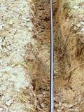 Οικοδόμηση των γραμμών μεταλλικών και καλωδίων οπτικών ινών Τοποθέτηση του υπόγειου καλωδίου σύνδεσης δικτύων ρυμούλκησης Στοκ Εικόνες