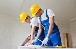 Οικοδόμοι που εργάζονται με τα βραχίονας-πριόνια στοκ φωτογραφία με δικαίωμα ελεύθερης χρήσης