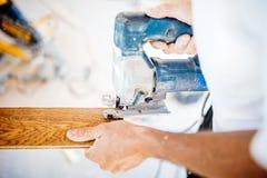 οικοδόμος βιομηχανικών εργατών που εργάζεται με το ηλεκτρικά τορνευτικό πριόνι και το ξύλο Στοκ Φωτογραφίες