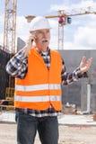 Οικοδόμος μηχανικών στο εργοτάξιο οικοδομής που μιλά στο τηλέφωνο Στοκ Φωτογραφίες