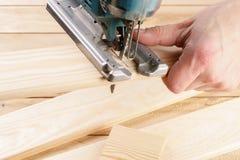 Οικοδόμος ξυλουργών ατόμων που εργάζεται με το ηλεκτρικά τορνευτικό πριόνι και το ξύλο Στοκ Φωτογραφία
