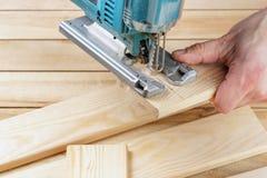 Οικοδόμος ξυλουργών ατόμων που εργάζεται με το ηλεκτρικά τορνευτικό πριόνι και το ξύλο Στοκ εικόνα με δικαίωμα ελεύθερης χρήσης