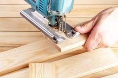 Οικοδόμος ξυλουργών ατόμων που εργάζεται με το ηλεκτρικά τορνευτικό πριόνι και το ξύλο Στοκ Εικόνες
