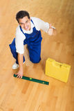 Οικοδόμος που ελέγχει το πάτωμα με το επίπεδο Στοκ φωτογραφία με δικαίωμα ελεύθερης χρήσης