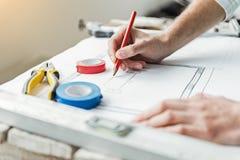 Οικοδόμος που διορθώνει το δεδομένο σχέδιο για χαρτί Στοκ Εικόνες