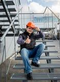 Οικοδόμος στη συνεδρίαση κρανών στη σκάλα μετάλλων και την παρουσίαση u αντίχειρων Στοκ φωτογραφία με δικαίωμα ελεύθερης χρήσης