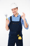Οικοδόμος στο σκληρό γαλλικό κλειδί και την παρουσίαση εκμετάλλευσης καπέλων εντάξει σημαδιού Στοκ Εικόνες