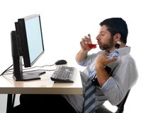 Οινοπνευματώδης συνεδρίαση ουίσκυ κατανάλωσης επιχειρησιακών ατόμων που πίνεται στο γραφείο με τον υπολογιστή Στοκ Εικόνες
