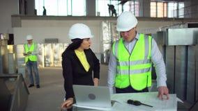 Οι άνδρες και γυναίκες εργαζόμενοι αποθηκών εμπορευμάτων εξετάζουν έναν φορητό προσωπικό υπολογιστή και συζητούν τις διοικητικές  απόθεμα βίντεο