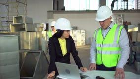 Οι άνδρες και γυναίκες εργαζόμενοι αποθηκών εμπορευμάτων εξετάζουν έναν φορητό προσωπικό υπολογιστή και συζητούν τις διοικητικές  φιλμ μικρού μήκους