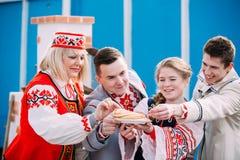 Οι άνθρωποι έντυσαν στα εθνικά λαϊκά ενδύματα που θέτουν με ένα πιάτο του π Στοκ εικόνες με δικαίωμα ελεύθερης χρήσης