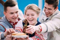 Οι άνθρωποι έντυσαν στα εθνικά λαϊκά ενδύματα που θέτουν με ένα πιάτο Στοκ Φωτογραφίες