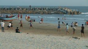 Οι άνθρωποι έχουν την κολύμβηση υπολοίπου περπατώντας κατά μήκος της παραλίας άμμου απόθεμα βίντεο