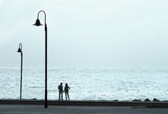 Οι άνθρωποι αγαπούν εγκαταλειμμένα φω'τα θάλασσας ακτών περιπάτων τα χέρι το βράδυ στοκ εικόνες