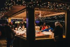 Οι άνθρωποι αγοράζουν τα γλυκά στο στάβλο μιγμάτων επιλογών ` ν ` στην έκθεση χειμερινών χωρών των θαυμάτων στο Λονδίνο Στοκ Φωτογραφίες