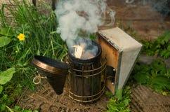 Οι άνθρωποι ανάβουν τη συσκευή για τις μέλισσες με τον καπνό στοκ φωτογραφία