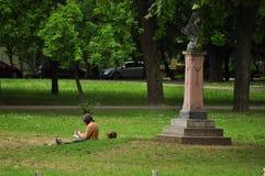 Οι άνθρωποι ανάγνωσης σε ένα κοινό σταθμεύουν με το dachshund Στοκ εικόνα με δικαίωμα ελεύθερης χρήσης