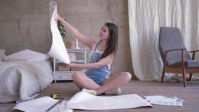 Οι άνθρωποι ανακαίνισης, συμπαθητικό κορίτσι στις φόρμες τζιν κοιτάζο απόθεμα βίντεο