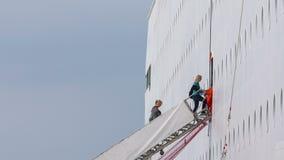 Οι άνθρωποι αναρριχούνται στα απότομα σκαλοπάτια στον πίνακα σε ένα τεράστιο ταχύπλοο σκάφος