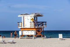 Οι άνθρωποι απολαμβάνουν την παραλία δίπλα σε έναν πύργο lifeguard Στοκ Εικόνες