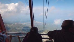 Οι άνθρωποι είναι εσωτερικό τελεφερίκ εξετάζουν τα σύννεφα και το πανόραμα της τουρκικής ακτής, πάνω από Tahtali απόθεμα βίντεο