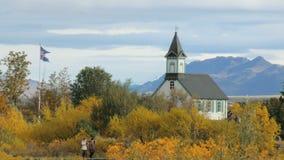 Οι άνθρωποι είναι strolling σε ένα εθνικό ισλανδικό πάρκο στην ημέρα φθινοπώρου κοντά στο παλαιό κτήριο ενάντια στο βουνό φιλμ μικρού μήκους