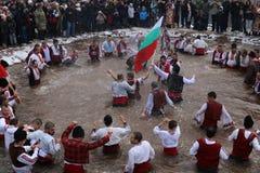 """Οι άνθρωποι εκτελούν τον εθνικό χορό """"Horo """"στα παγωμένα νερά του ποταμού Iskar στο χωριό Zverino στοκ φωτογραφίες"""
