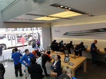 Οι άνθρωποι εξετάζουν τα προϊόντα και τη συζήτηση στα υφάσματα πωλήσεων μέσα στη Apple Stor Στοκ Φωτογραφίες