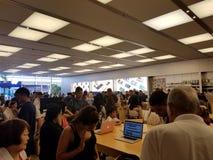 Οι άνθρωποι εξετάζουν το lap-top και άλλα προϊόντα σε πολυάσχολο το retai της Apple Στοκ Εικόνα
