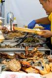 Οι άνθρωποι εξυπηρετούν τα τρόφιμα σε έναν στάβλο τροφίμων οδών Στοκ Εικόνες