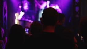 Οι άνθρωποι επιδοκιμάζουν σε μια συναυλία βράχου φιλμ μικρού μήκους