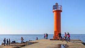 Οι άνθρωποι επισκέπτονται τον κόκκινο φάρο, που βρίσκεται στο θαλάσσιο λιμένα της Ρήγας, Λετονία Στοκ φωτογραφία με δικαίωμα ελεύθερης χρήσης