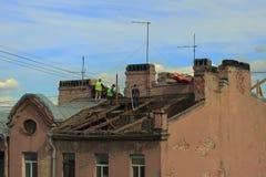 Οι άνθρωποι επισκευάζουν την παλαιά στέγη στοκ εικόνα με δικαίωμα ελεύθερης χρήσης