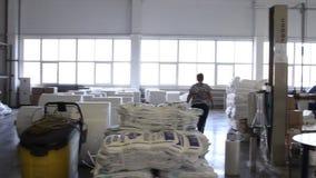 Οι άνθρωποι εργάζονται στη μεγάλη αποθήκη εμπορευμάτων με τα αγαθά στο εργοστάσιο φιλμ μικρού μήκους