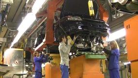 Οι άνθρωποι εργάζονται στη συνέλευση των αυτοκινήτων Lada Kalina (μοντάρισμα μηχανών) στο μεταφορέα του εργοστασίου AutoVAZ, στις απόθεμα βίντεο