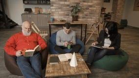 Οι άνθρωποι εργάζονται στη coworking διαστημική συνεδρίαση στις τσάντες φασολιών απόθεμα βίντεο