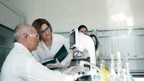 Οι άνθρωποι εργάζονται στο κλινικό εργαστήριο με το μικροσκόπιο απόθεμα βίντεο