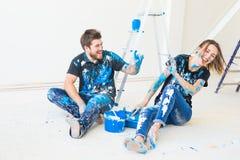 Οι άνθρωποι, η έννοια redecoration και σχέσης - νέο αστείο ζεύγος που κάνει την ανακαίνιση στο νέο διαμέρισμα και έχουν τη διασκέ στοκ φωτογραφία