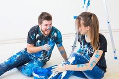 Οι άνθρωποι, η έννοια redecoration και σχέσης - νέο αστείο ζεύγος που κάνει την ανακαίνιση στο νέο διαμέρισμα και έχουν τη διασκέ στοκ φωτογραφίες