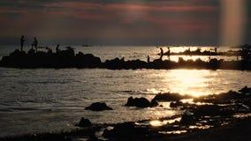 Οι άνθρωποι ηλιοβασιλέματος λούζουν, στην παραλία θάλασσας κολυμπήστε τις βάρκες, παφλασμός κυμάτων για την ακτή απόθεμα βίντεο
